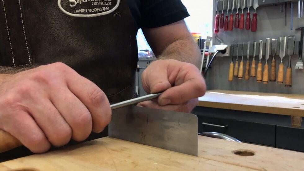 Daniel lägger en krok på sickeln med hjälp av ett stickelstål.