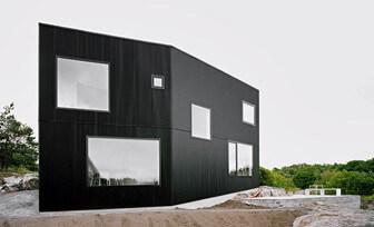 Svart fasad med stora fönster
